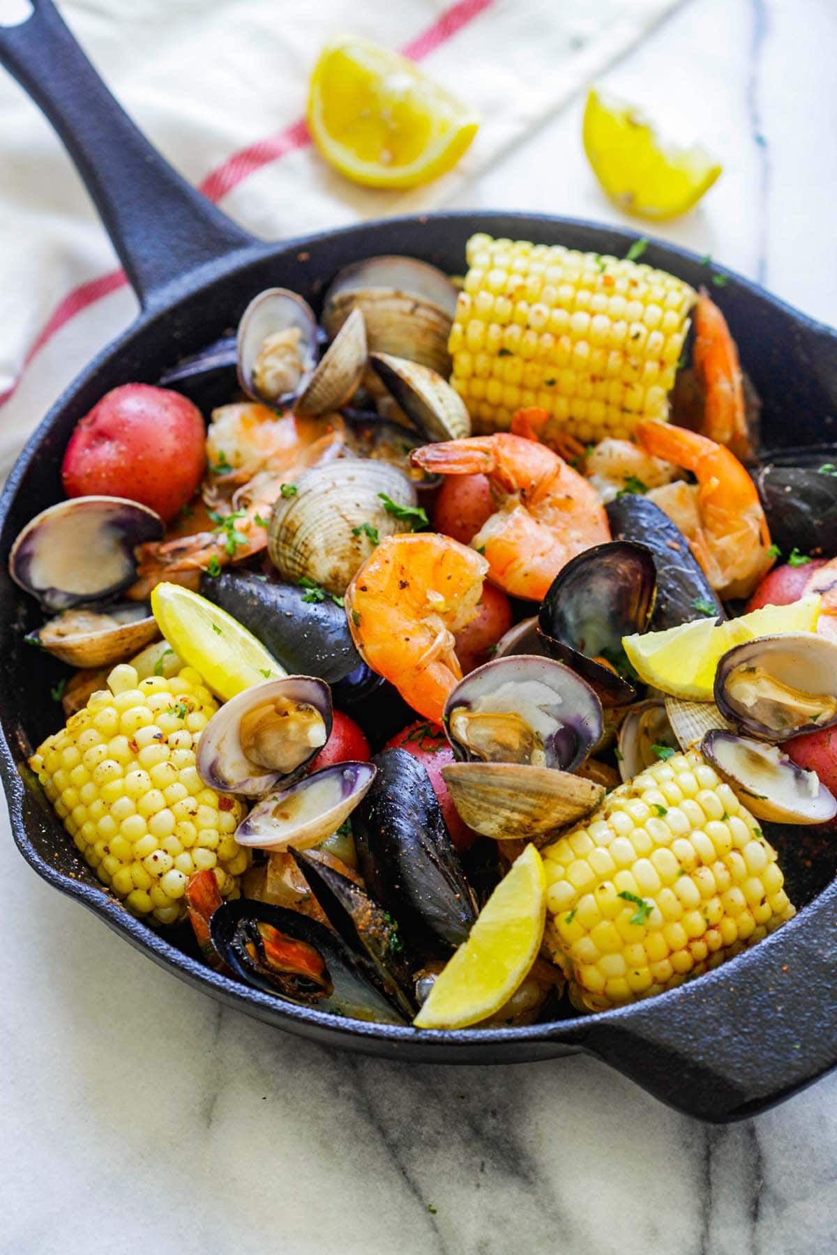 Easy clambake (clam boil) in a skillet with clams, mussels, shrimp, corn and potatoes.