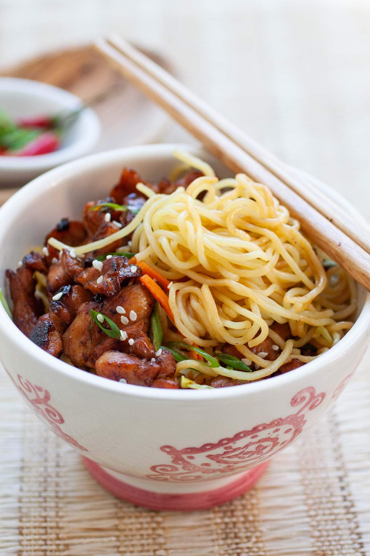 Delicious stir-fried egg noodles with chicken in a bowl, ready to be served.