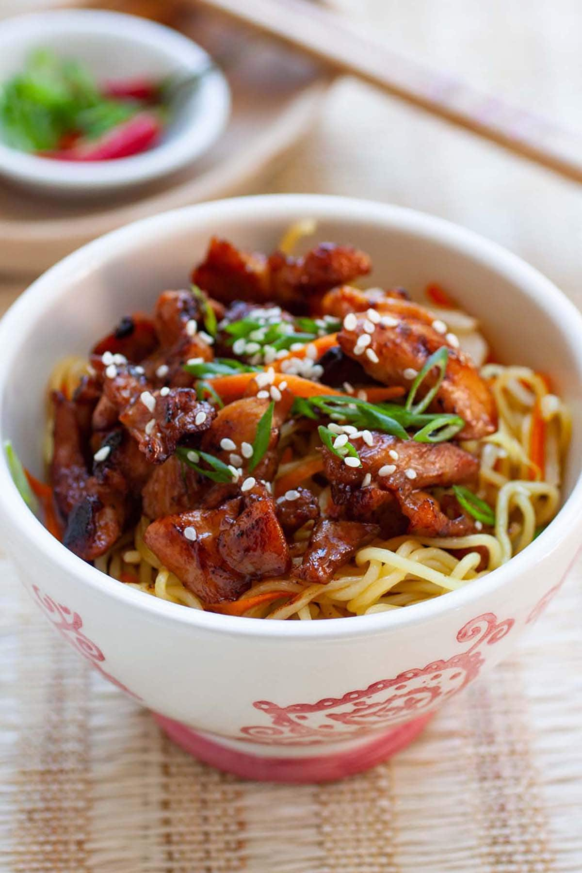 Chicken stir-fried noodles complete with carrots and green onions in a bowl.