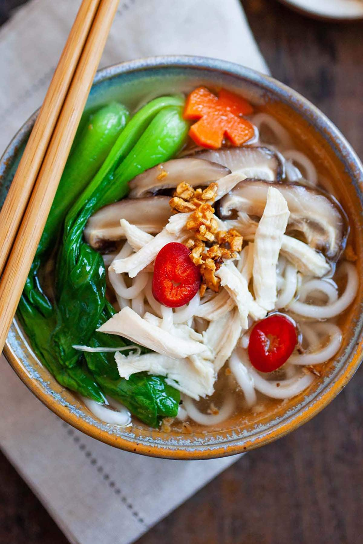 Asian noodle soup with chicken, bok choy vegetables and noodles in a bowl.