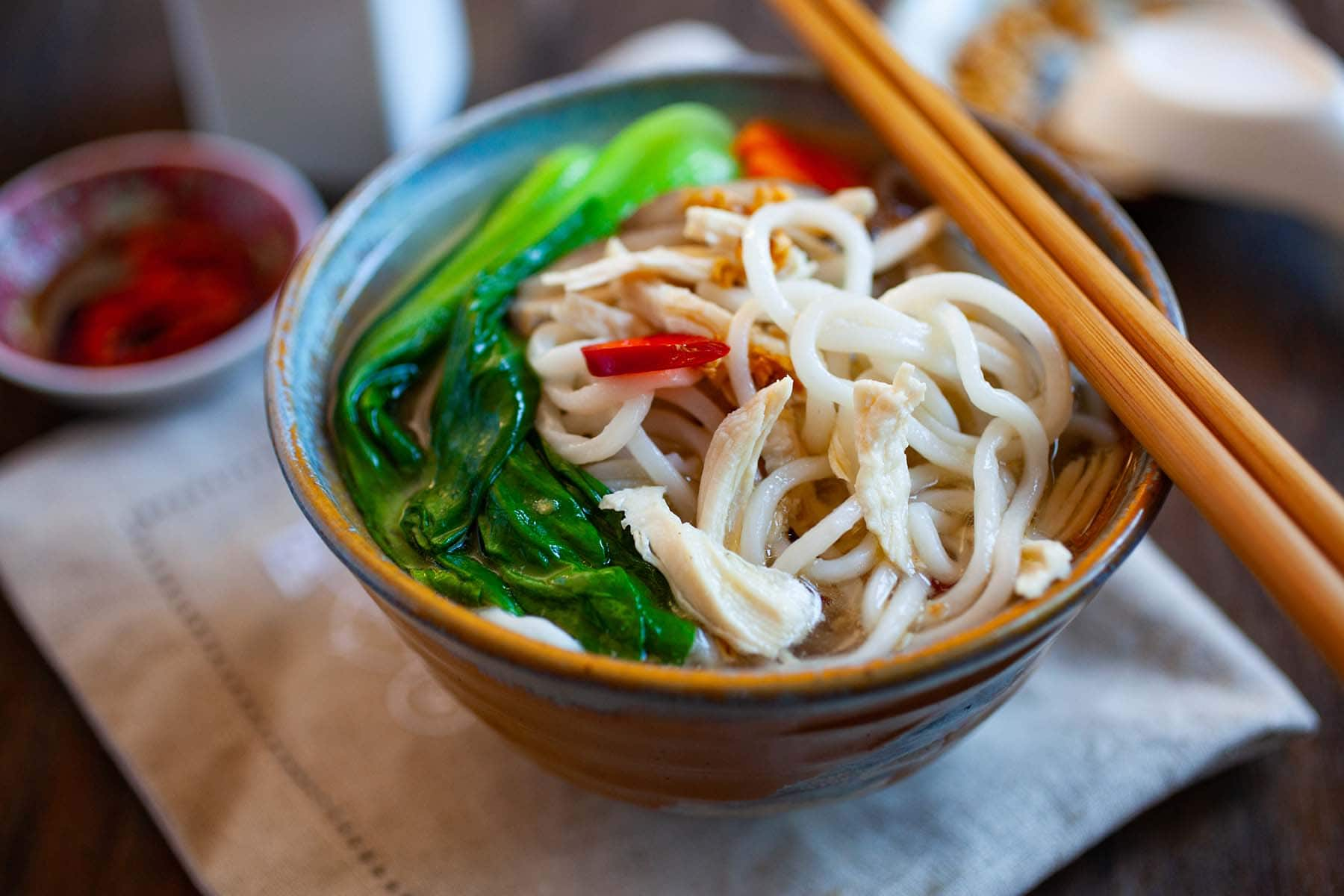 Chinese noodle soup with chicken, bok choy and noodles in a white bowl.