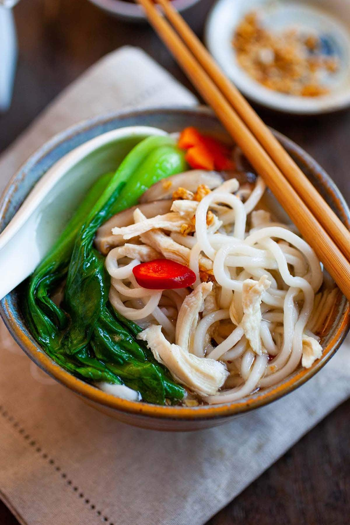 Chinese Chicken Noodle Soup with chicken broth, noodles and bok choy in a bowl.