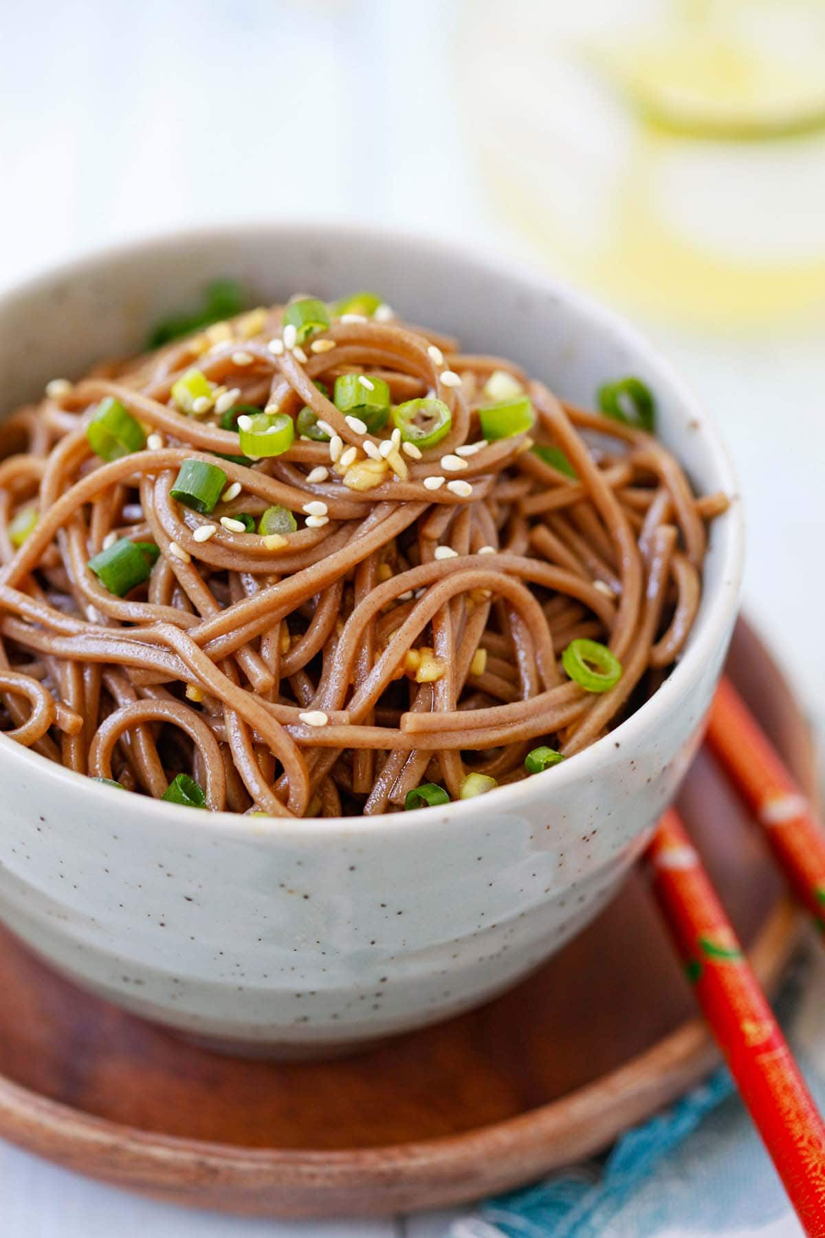 Healthy and easy Ginger Soy Soba topped with chopped scallions in a bowl.