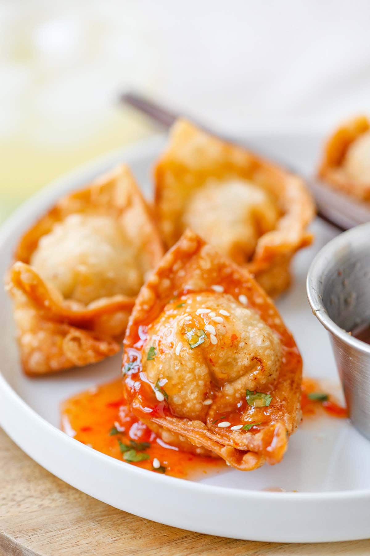 Wonton, fried to golden brown and covered in sweet and sour sauce on plate.