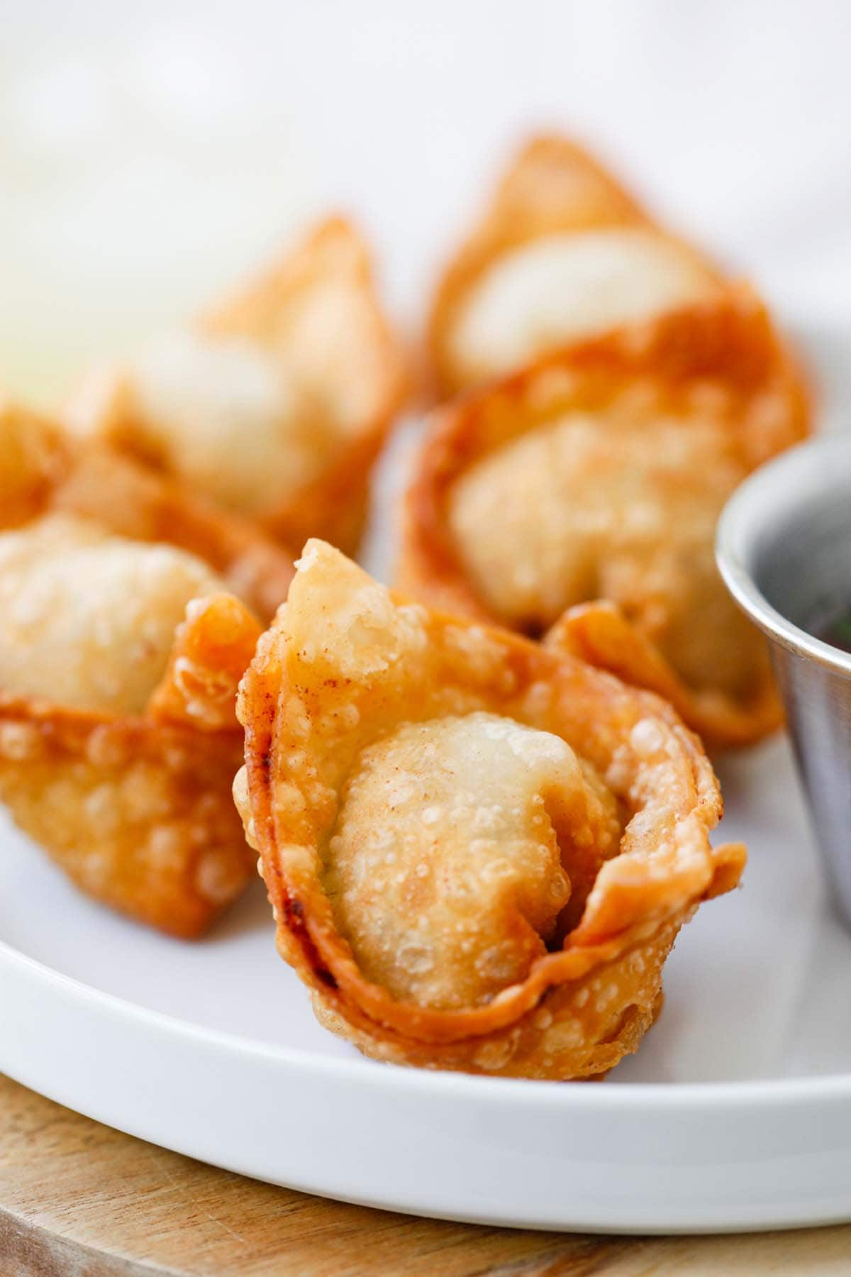 Perfectly brown fried wontons on serving dish with side of sweet and sour sauce.