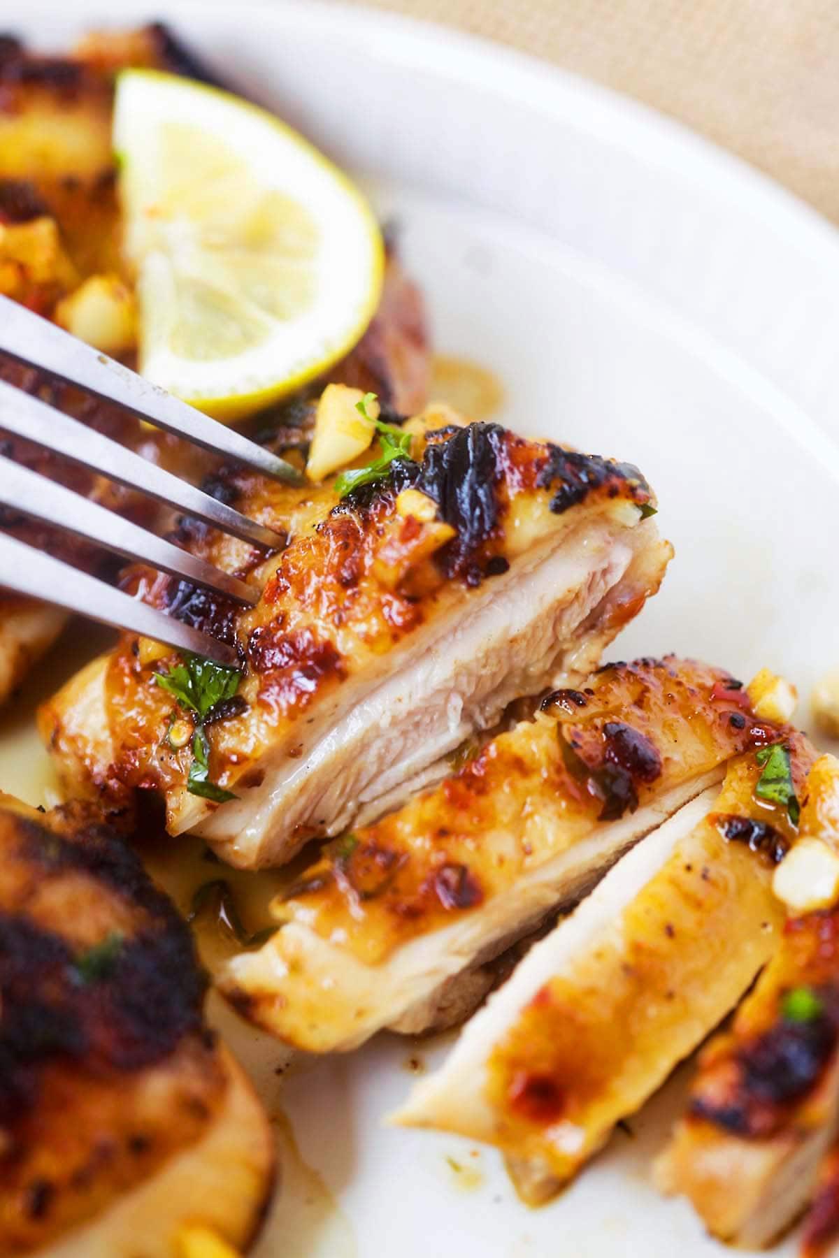 Lemon Garlic Chicken Served On Plate, cut, ready to be eaten.