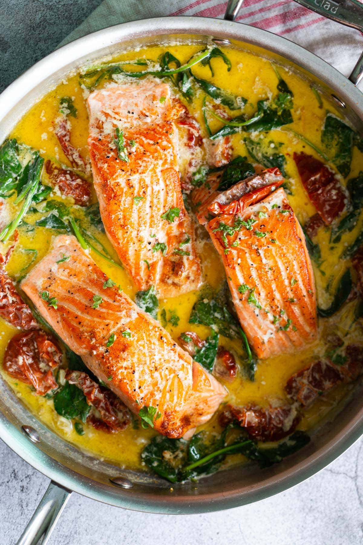 Tuscan salmon recipe with spinach, garlic, butter and sun-dried tomatoes.