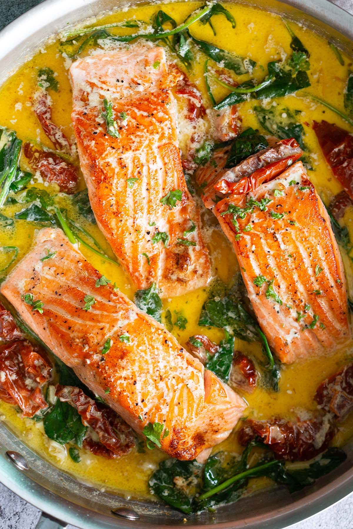 Tuscan salmon in a skillet.