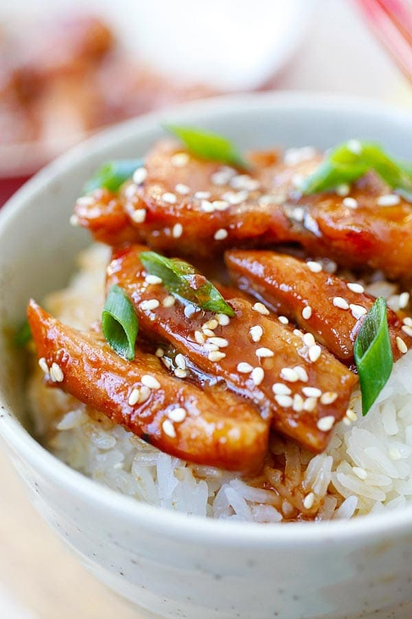 Teriyaki chicken with steamed rice, teriyaki sauce, white sesame and chopped scallion in a Japanese bowl.